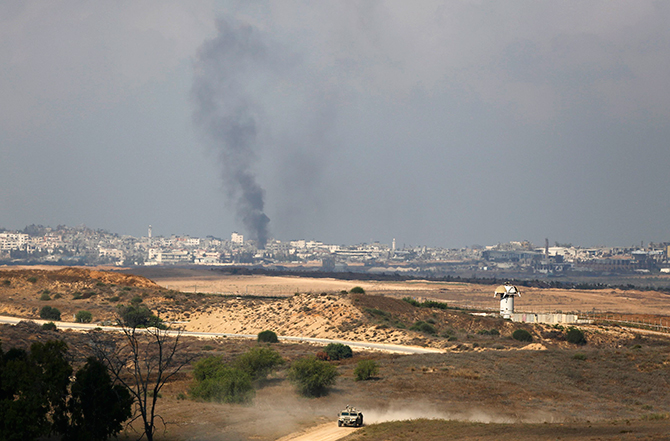 Rising smoke after an Israeli strike can be seen in the Gaza Strip as an Israeli military vehicle drives on the Israeli side of the border August 8, 2014. The Israeli military responded with air strikes at
