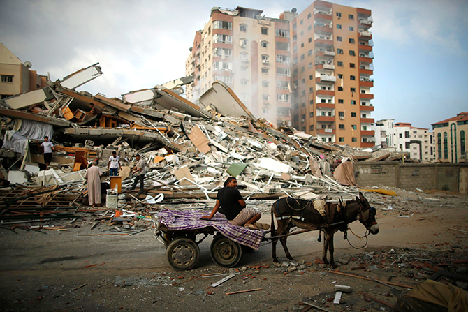 Palestinians ride a donkey cart past the rubble of a residential tower, which witnesses said was destroyed in an Israeli air strike in Gaza City August 24, 2014. Photo: Reuters