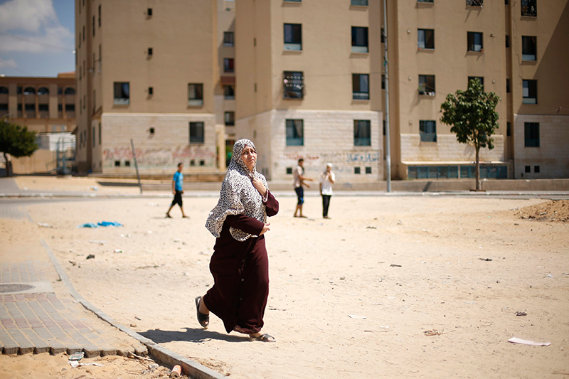 A Palestinian woman flees her house following what witnesses said was a nearby air strike on an apartment in Beit Lahiya in the northern Gaza Strip August 10, 2014. Photo: Reuters
