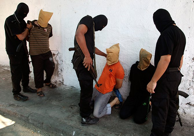 Hamas militants grab Palestinians suspected of collaborating with Israel, before executing them in Gaza City August 22, 2014. Hamas militants killed seven Palestinians suspected of collaborating with Israel in a public execution in a central Gaza square on Friday, witnesses and a Hamas website said. Photo: Reuters
