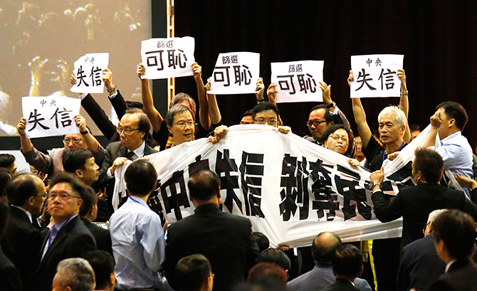 Pro-democracy lawmakers hold up a banner and placards to protest as Li Fei (not pictured), deputy general secretary of the National People's Congress (NPC) standing committee, speaks during a briefing session in Hong Kong September 1, 2014. Photo: Reuters