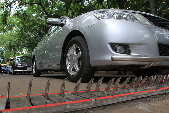 A car can be seen passing over the spikes. The spikes retract back to the roads if a car approaches from the right direction. Photo: Palash Khan
