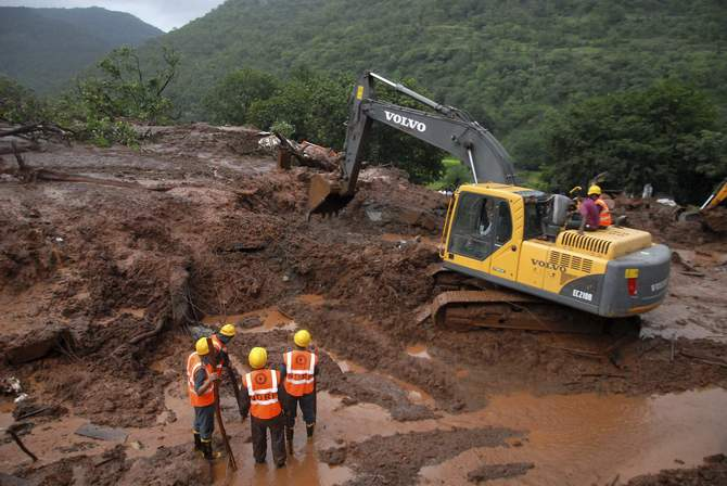 National Disaster Response Force (NDRF) personnel clear the debris from the site of a landslide at Malin village, in the western Indian state of Maharashtra July 30, 2014. Photo: Reuters