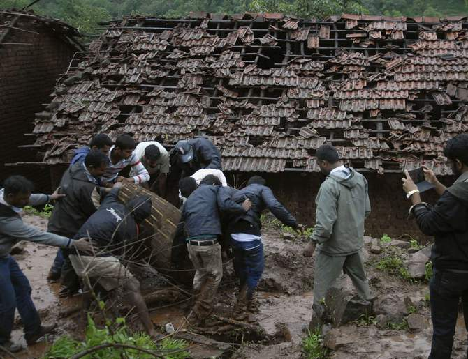 Rescue workers and volunteers clear the debris from the site of a landslide at Malin village in the western Indian state of Maharashtra July 30, 2014. Heavy rain triggered a landslide in India on Wednesday burying up to 150 people and rescuers were struggling through mud to try to reach them, a disaster official said. Photo: Reuters