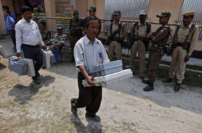 Election officials carry Electronic Voting Machines (EVM) as Indian security personnel stand guard at a distribution centre ahead of general elections in Jorhat district, in the northeastern Indian state of Assam April 6, 2014. Photo: Reuters