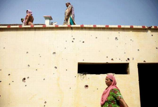 Women walk past a residential building with bullet marks allegedly fired from the Pakistan side at the India-Pakistan international border area of RS Pura on August 22, 2014. Photo: AP