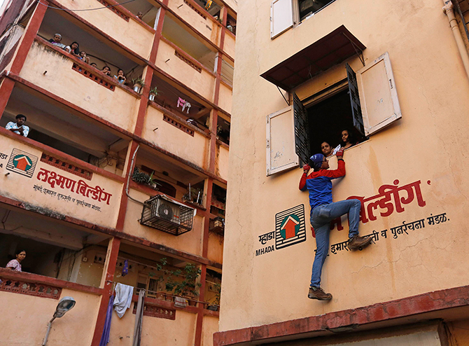 Gaurav Sharma, an independent candidate also known as the Indian Spider-Man, climbs a residential building during an election campaign in Mumbai on Friday. Photo: Reuters