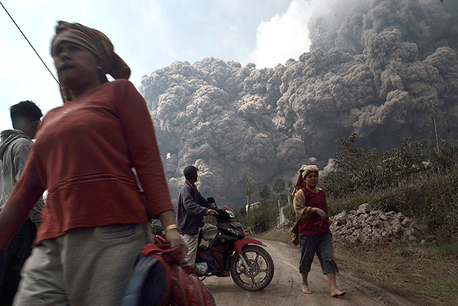 Villagers run as Mount Sinabung erupts at Sigarang-Garang village in Karo district, Indonesia's North Sumatra province February 1, 2014.