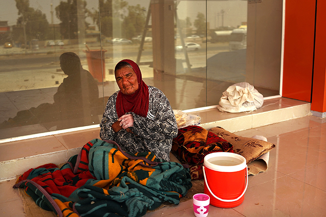 An Iraqi woman rests on the floor of an empty store at a construction site where she is living with dozens of other displaced Iraqis who have fled the fighting in and around the city of Mosul on June 29, 2014 in Kalak, Iraq. Photo: Getty Images