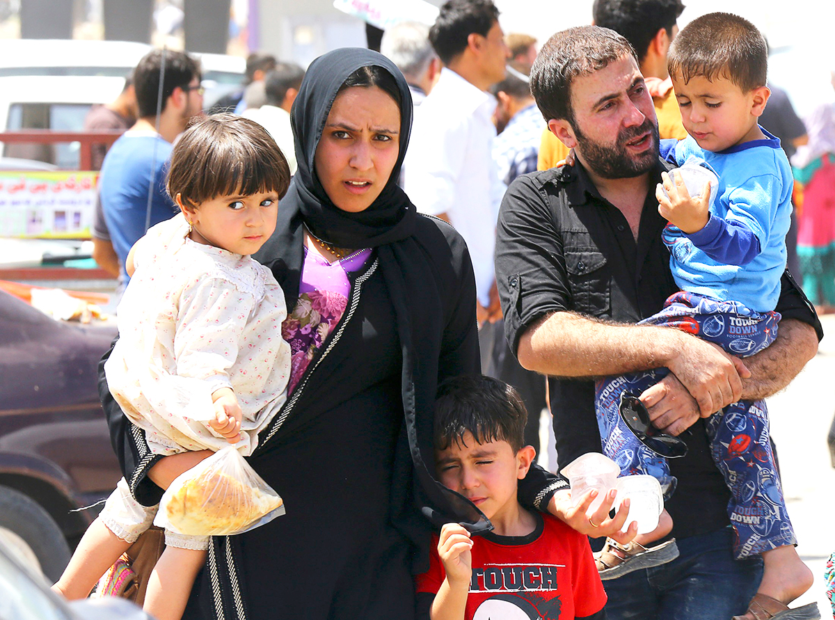 A family fleeing the violence in the Iraqi city of Mosul waits at a checkpoint in outskirts of Arbil, in Iraq's Kurdistan region, June 10, 2014. Photo: Reuters