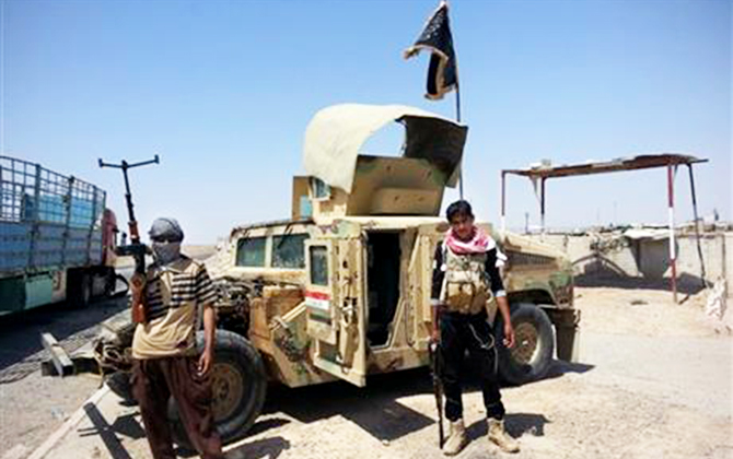 Al-Qaeda inspired militants stand with captured Iraqi Army Humvee at a checkpoint outside Beiji refinery, some 250 kilometers north of Baghdad, Iraq, on June 19, 2014. Photo: AP