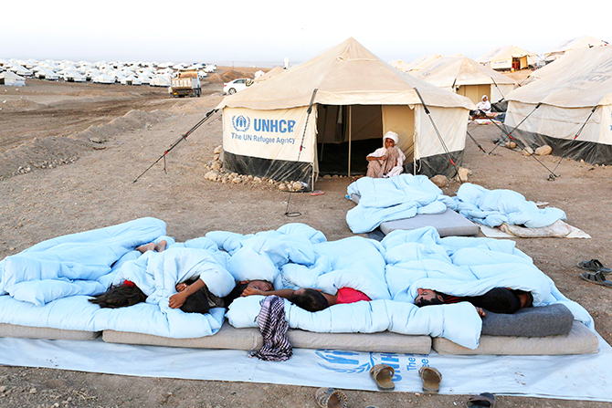 Displaced people from the minority Yazidi sect, who fled violence in the Iraqi town of Sinjar, sleep on the ground at Bajed Kadal refugee camp, southwest of Dohuk province, August 23, 2014. Photo: Reuters