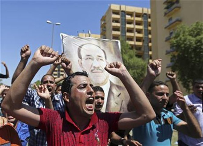 Iraqis chant pro-government slogans and display placards bearing a picture of embattled Prime Minister Nouri al-Maliki during a demonstration in Baghdad, Iraq, Monday, Aug. 11, 2014. Photo:AP