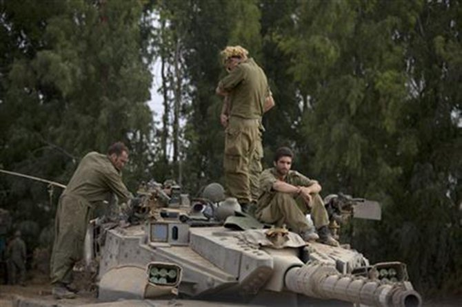 Israeli soldiers work on a tank near the Israel and Gaza border Thursday, July 24, 2014.Photo: AP