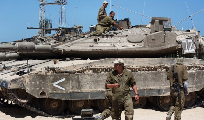Israeli soldiers work on their Merkava tanks in an army deployment area near Israel's border with the Gaza Strip on July 11. Photo: Getty Images