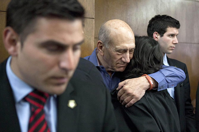 This Reuters photo taken on March 31, 2014 shows former Israeli Prime Minister Ehud Olmert (2nd L) hugs a woman while waiting to hear his verdict at the Tel Aviv District Court.
