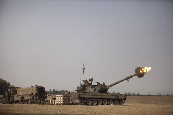 An Israeli artillery cannon fires a shell on July 12, 2014 on Israel's border with the Gaza Strip. Israel's operation 'Protective Edge' has entered its fifth day as the IDF continue to carry out massive airstrikes across the Gaza Strip, killing more than 120 people, the majority of whom are civilians. Photo: Getty Images