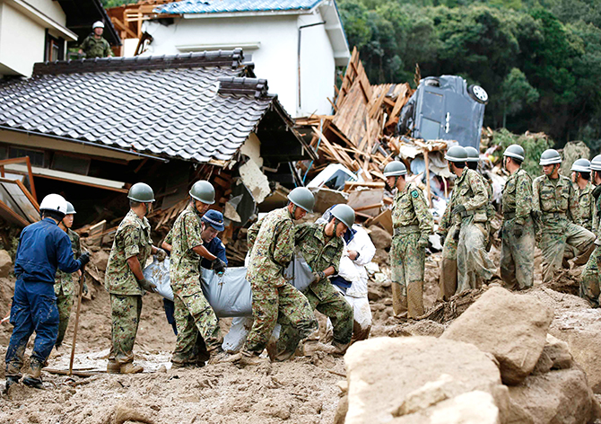 Japan Self-Defense Force (JSDF) soldiers and police officers carry a victim in a plastic bag at a site where a landslide swept through a residential area at Asaminami ward in Hiroshima, western Japan, August 20, 2014. Photo: Reuters