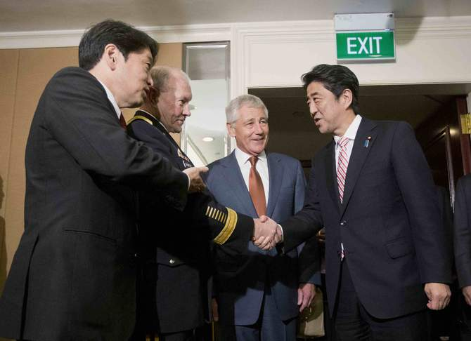 Japanese Defense Minister Itsunori Onodera (L) and US Defense Secretary Chuck Hagel (2nd R) look on as US Chairman of the Joint Chiefs of Staff General Martin Dempsey (2nd L) shakes hands with Japanese Prime Minister Shinzo Abe in Singapore May 30, 2014. Photo: Reuters
