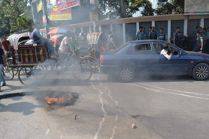 Students of Jagannath University burn wooden materials on the road in front of Jatiya Press Club in the capital during their sit-in programme Monday. The students have been demonstrating since February 12 demanding