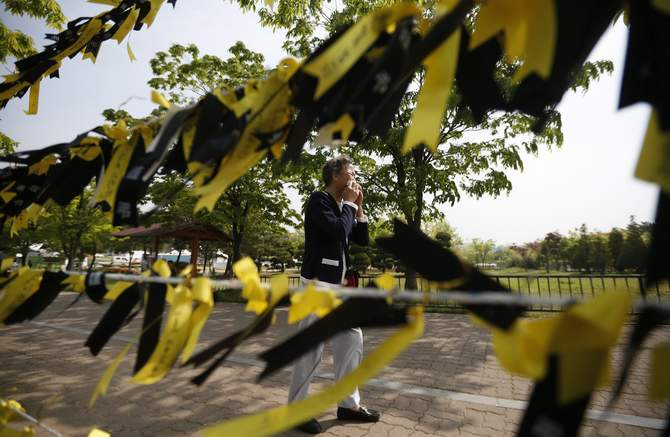 A mourner cries next to yellow ribbons dedicated to missing and dead passengers of sunken passenger ship Sewol, after paying tribute at the official memorial altar in Ansan May 2, 2014. Photo: Reuters