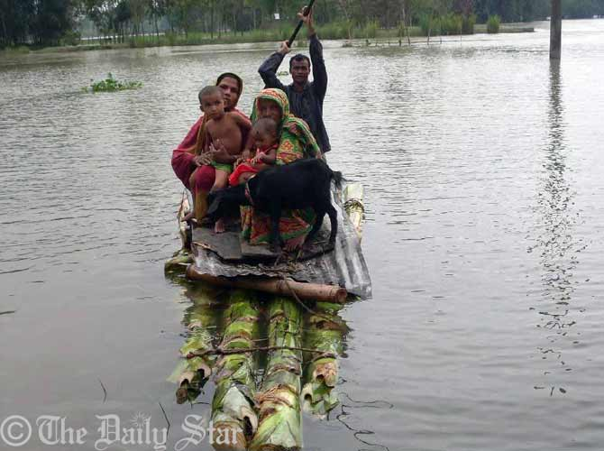 Flood-hit people leave houses as their village goes under overflow water of the Teesta river Thursday morning. Photo: STAR