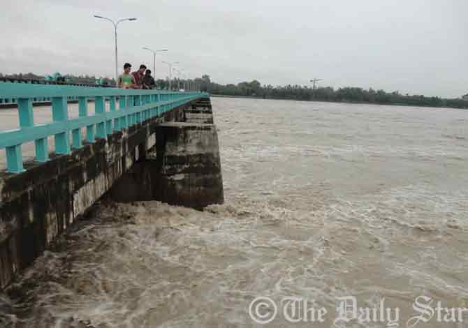 The river-water flows 30 centimetres above of danger mark at the Teesta Barrage point in Dowani village of Hatibanda upazila in Lalmonirhat Thursday morning. Photo: STAR