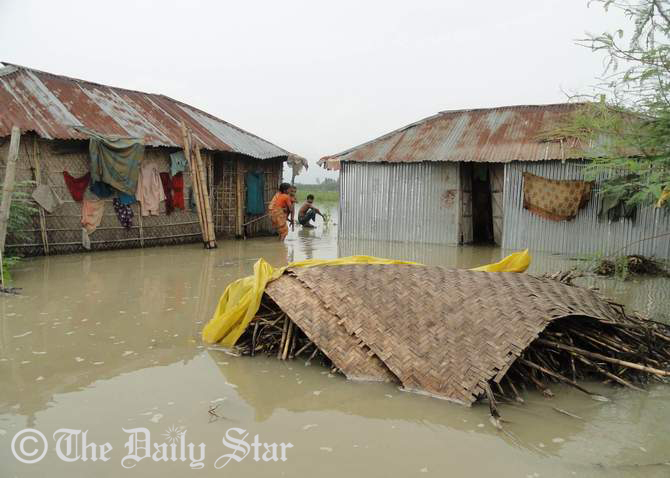 Residents leave their houses after water from the Teesta river floods houses in Gobordhan village in Aditmari upazila of Lalmonirhat district. Photo: STAR