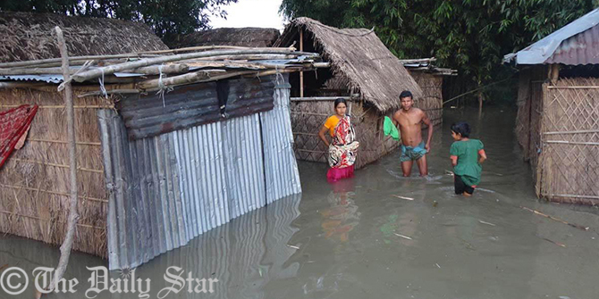Villagers are seen standing in knee-deep water near their houses at Kuniagachh village of Lalmonirhat Sadar upazila. Fresh areas at 40 villages in the district are flooded on Thursday due to overflow of the Teesta water. Photo: STAR