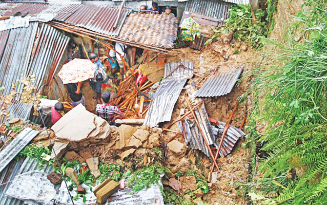 A mudslide induced by heavy rain destroys a home at the foot of a hill in Lalkhan Bazar in Chittagong city, killing two persons on July 28, 2013. Many families decided to stay in places identified as high risk to landslides even though the authorities concerned had asked them to move to safer places. Star file photo