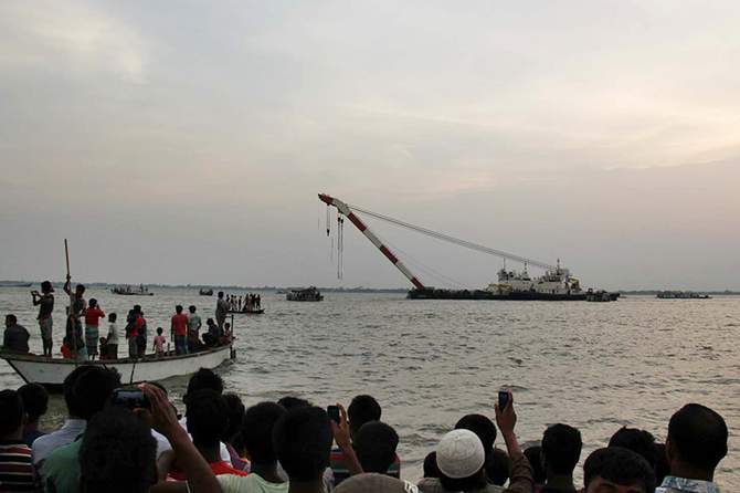 This May 15 photo shows people gather on the bank of Meghna river where launch MV Miraj-4 capsized, killing at least 56 people. A salvage ship is seen in the photo trying to recover the vessel.