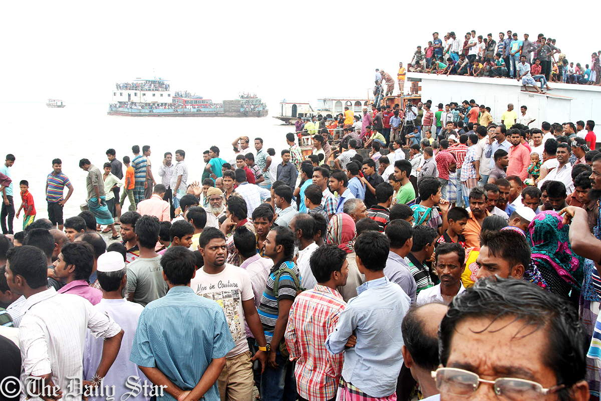 Several hundred people throng the bank of Padma Tuesday to see the rescue operation of the sunken launch. Photo: Sk Enamul Huq