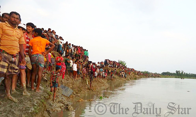 Relatives and villagers gather on the bank of Golachipa river Saturday afternoon where the launch capsize. Photo: Star