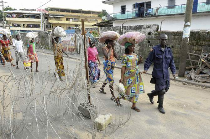 People living outside the Ebola quarantine area of Westpoint walk at a checkpoint while carrying food and essentials for their relatives in quarantine, in Monrovia August 23, 2014. In an attempt to contain the virus, Liberia imposed a quarantine in West Point, a large slum in the capital Monrovia, on August 19. Photo: Reuters