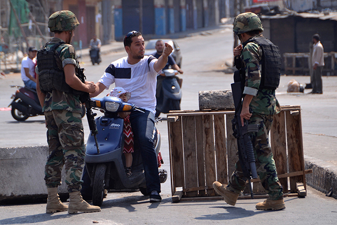 A civilian on a scooter talks to Lebanese army soldiers as he tries to make his way through a blocked road in Lebanon's northern port city of Tripoli August 5, 2014. Photo: Reuters