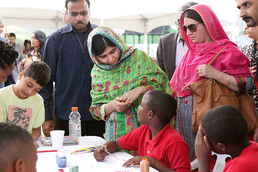 Pakistani schoolgirl activist Malala Yousafzai (C) talks to a boy taking part in a workshop at the Emancipation Village at Queen's Park Savannah, in Port of Spain July 31, 2014. Seen at left is Malala's brother Atal Khan Yousafzai and at right is her mother Toorpekai Yousafzai. Photo: Reuters