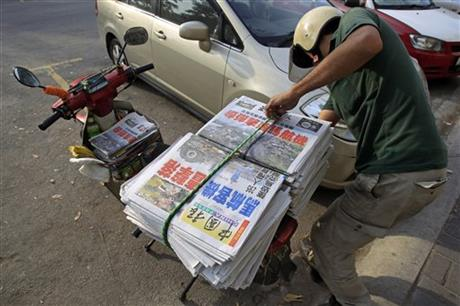 A newspaper delivery man prepares to unload Chinese newspapers carrying headline stories and pictures of Thursday's Malaysia Airlines plane shot down, in Shah Alam, outside Kuala Lumpur, Malaysia, Friday. Photo: AP