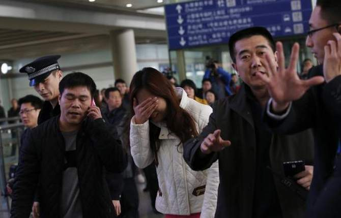 A woman (C), believed to be the relative of a passenger onboard Malaysia Airlines flight MH370, covers her face as she cries at the Beijing Capital International Airport in Beijing on March 8, 2014. Photo: Reuters