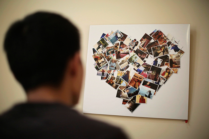 Zhang Zhiliang, 27-year-old Tianjin resident, looks at a board covered with pictures of his fiancee Li Jie, a passenger on board the missing Malaysia Airlines MH370, at their leased apartment in Tianjin, on Saturday. Li, who worked as an executive assistant at a firm in Beijing, went on a business trip to Malaysia on March 6. Zhang and Li were engaged earlier this year and planned to register for their marriage on March 23. Photo: Reuters