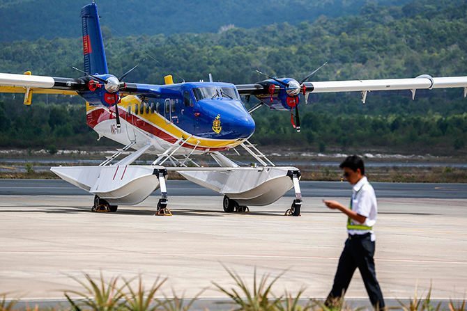 A Vietnamese worker walks past a search and rescue aircraft from Vietnam, at Phu Quoc Airport in Phu Quoc Island, March 12, 2014. Vietnam said on Wednesday it was scaling back the search in Vietnamese waters for a Malaysian Airlines jetliner missing for four days, a senior Vietnamese official said. Photo: Reuters