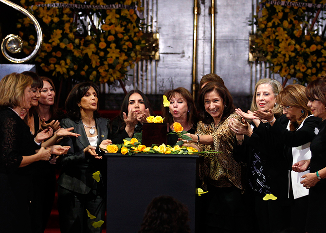 Women blow yellow rose petals over an urn containing the ashes of late Colombian Nobel laureate Gabriel Garcia Marque during a public viewing in the Palace of Fine Arts in Mexico City on Monday. Photo: Reuters