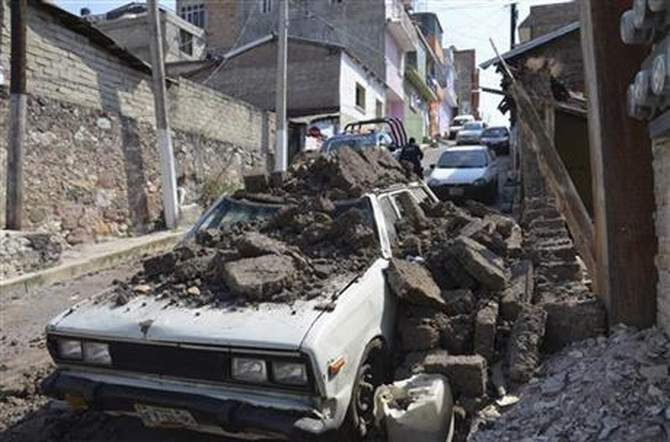 A parked car suffered damage when an adobe wall collapsed on it after a strong earthquake shook Chilpancingo, Mexico, Friday morning, April 18, 2014. A powerful magnitude-7.2 earthquake shook central and southern Mexico but there were no early reports of major damage or casualties. Photo: AP