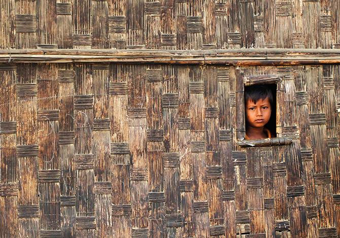 A boy looks from his temporary shelter at a Rohingya refugee camp as Myanmar's government embarks on a national census, in Sittwe on Wednesday. At least 20,000 people in displacement camps around Sittwe will run out of drinking water within 10 days, while food stocks will run out within two weeks, imperilling thousands more. Photo: Reuters
