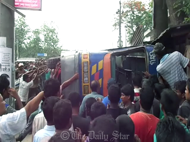 Locals try to move the bus that overturned while taking a U-turn in full speed at Meherpur College Intersection in Meherpur town on Thursday. Four people were killed and 30 injured in the accident. Photo: Star