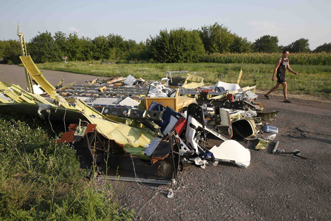 A local resident walks past debris at the site where Malaysia Airlines flight MH17 crashed, near Petropavlivka village in the Donetsk region July 23, 2014. Photo: Reuters
