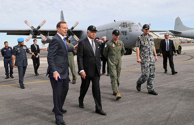 Australia's Prime Minister Tony Abbott (L) and Malaysia's Prime Minister Najib Razak tour the tarmac of RAAF Base Pearce with Australian Air Force Group Commander Craig Heap (3rd R) and Commodore Peter Leavy (2nd R), commander of join task force 658, near Perth on Thursday. Najib visited the Australian search base for missing Malaysia Airlines Flight MH370 as a nuclear-powered submarine joined the near-four week hunt that has so far failed to find any sign of the missing airliner and the 239 people on board. Photo: Reuters