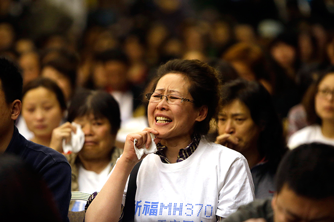 A relative of a passenger aboard Malaysia Airlines flight MH370 cries as she speaks to Malaysian representatives during a briefing at Lido Hotel in Beijing on April 21, 2014. Photo: Reuters