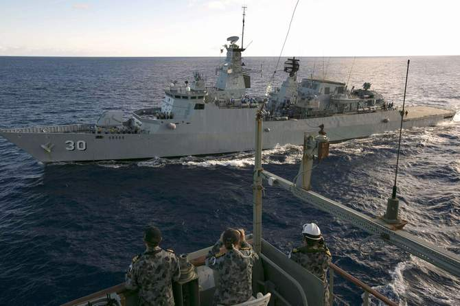 Crew aboard the Australian Navy ship HMAS Success look over to the Royal Malaysian Navy ship KD LEKIU during a Replenishment at Sea evolution in the southern Indian Ocean during the continuing search for the missing Malaysian Airlines flight MH370 in this picture released by the Australian Defence Force April 7, 2014. Photo: Reuters