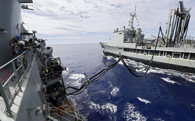Crew aboard the Australian Navy ship HMAS Perth watch lines as they are refuelled by HMAS Success during a replenishment at sea, as they continue to search for missing Malaysian Airlines flight MH370 in this picture released by the Australian Defence Force April 10, 2014.