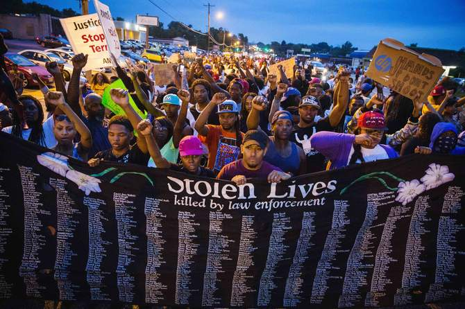 Protestors march and hold their fists aloft as they march during ongoing demonstrations in reaction to the shooting of Michael Brown in Ferguson, Missouri August 16, 2014. Photo: Reuters